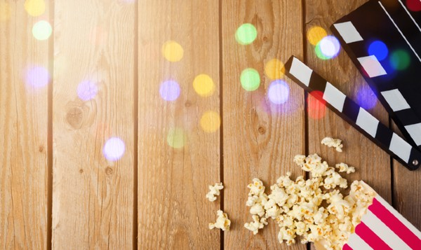 Popcorn and movie clapper on wood